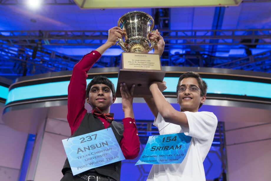 Ansun Sujoe, 13, of Fort Worth, Texas, left, and Sriram Hathwar, 14, of Painted Post, N.Y., raise the championship trophy after being named co-champions of the National Spelling Bee, on Thursday, May 29, 2014, in Oxon Hill, Md. (AP Photo/ Evan Vucci)
