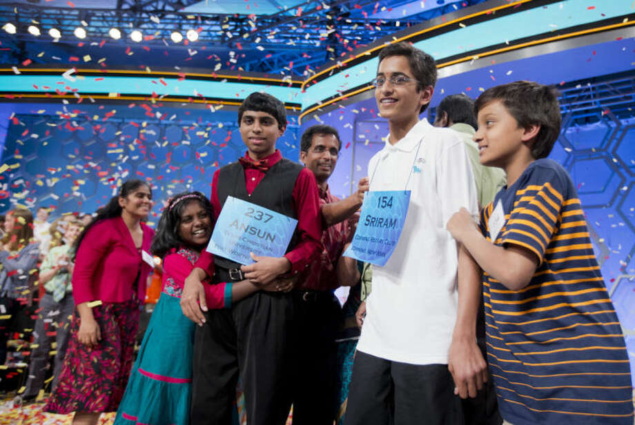The 2014 Scripps National Spelling Bee Co-Champions Ansun Sujoe, of Fort Worth, Texas, and Sriram Hathwar, of Painted Post, N.Y., celebrate with their family after winning the Scripps National Spelling Bee competition, Thursday, May 29, 2014, at National Harbor in Oxon Hill, Md. (AP Photo/Manuel Balce Ceneta)