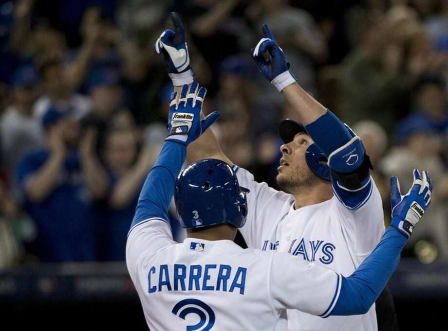 Toronto Blue Jays third baseman Danny Valencia, right, celebrates his three run home run with teammate Ezequiel Carrera (3) while playing against the New York Mets during the eighth inning of an interleague baseball game, Wednesday, June 17, 2015 in Toronto. (Nathan Denette/The Canadian Press via AP) MANDATORY CREDIT