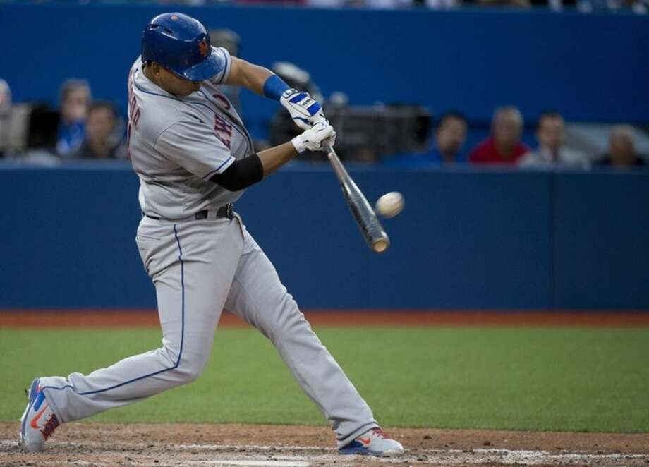 New York Mets third baseman Ruben Tejada hits a double against the Toronto Blue Jays during the fifth inning of an interleague baseball game, Wednesday, June 17, 2015 in Toronto. (Nathan Denette/The Canadian Press via AP) MANDATORY CREDIT