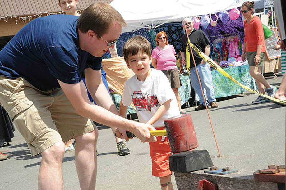 Brady Krupa 3, gets a hand hand from hisdad Doug with the strongman hammer Sunday at the Georgetown Day celebration. Photo/Matthew Vinci