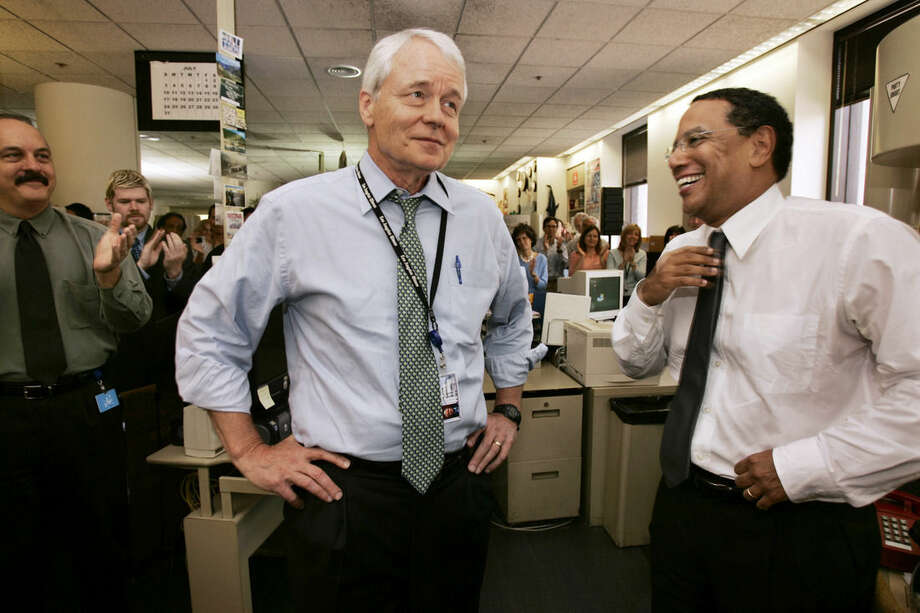 In this July 20, 2005 photo, Los Angeles Times editor John Carroll, center, announces his retirement and that managing editor Dean Baquet, right, will become executive vice president and editor, in the paper's newsroom in downtown Los Angeles. Carroll, former editor of the Baltimore Sun and the L.A. Times, which won 13 Pulitzer Prizes during his five-year tenure, died Sunday morning, June 14, 2015 at his home in Lexington, Ky., said his wife, Lee Carroll. He was 73. (Al Seib/Los Angeles Times via AP) NO SALES