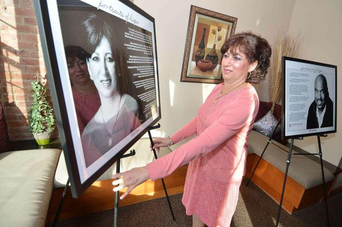 Hour Photo/Alex von Kleydorff Cancer Survivor Cathy Danna straightens the portrait of herself at the Portratis of Hope Reception in Stamford