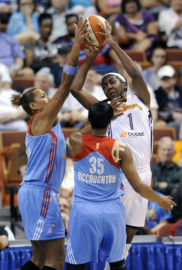 Connecticut Sun's Elizabeth Williams (1) fights for a rebound with Atlanta Dream's Angel McCoughtry (35) and Erika DeSouza during the first half of a WNBA basketball game in Uncasville, Conn., on Sunday, June 14, 2015. (AP Photo/Fred Beckham)