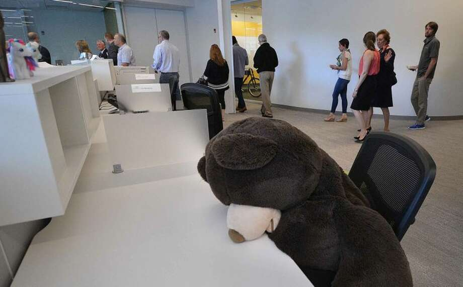 Hour Photo/Alex von Kleydorff A giant stuffed bear leans over his desk in the finance department as the tour moves through Cannondale Headquarters at I Park