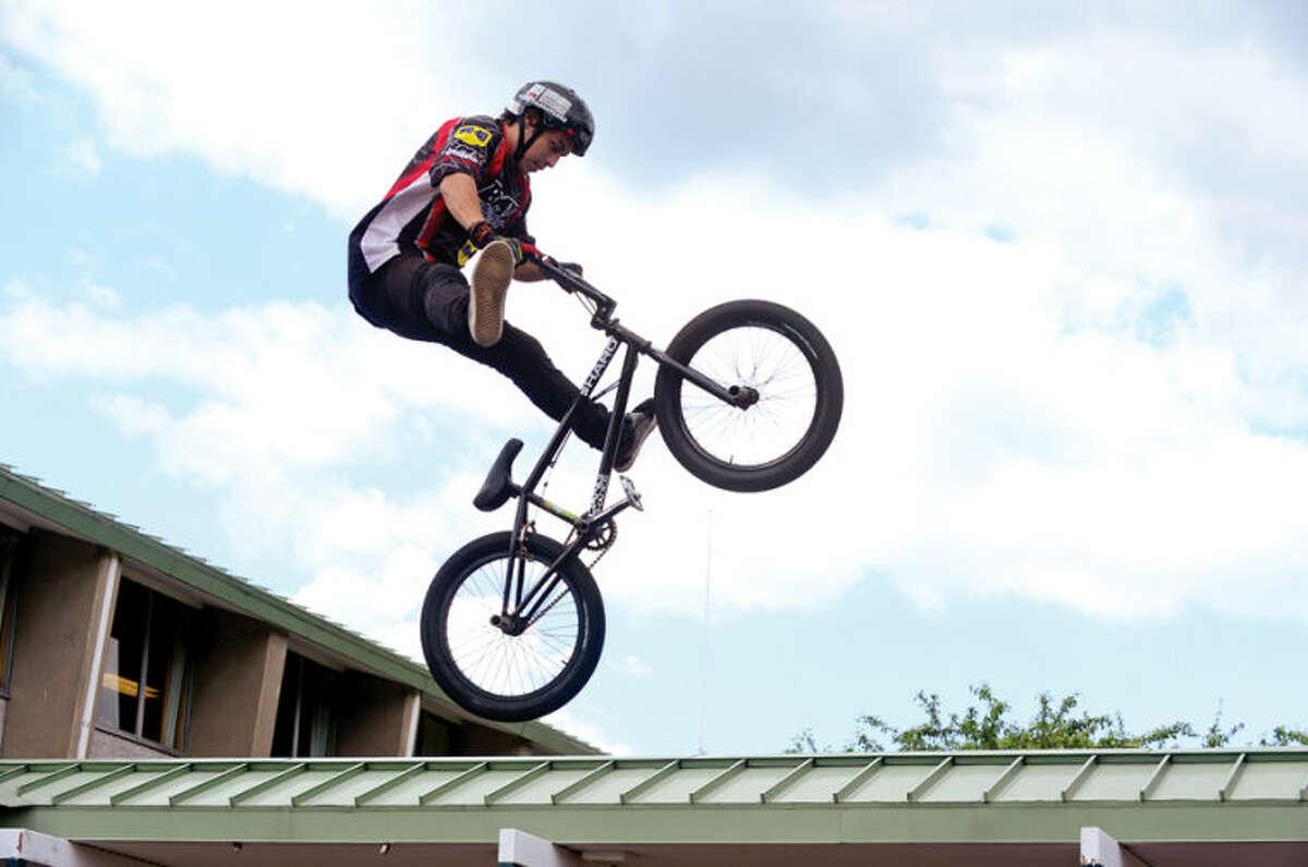 Hour photo / Erik Trautmann Stunt bicyclist Christian Maya performs as Fox Run Elementary School hosts the BMX troupe, Perfection On Wheels, Friday at the school.