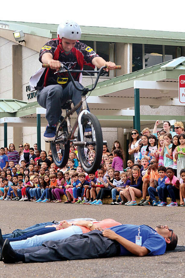Hour photo / Erik Trautmann Stunt rider Seth Bernard jumps over Fox Run Elementary School faculty as the school hosts the BMX troupe, Perfection On Wheels, Friday at the school.