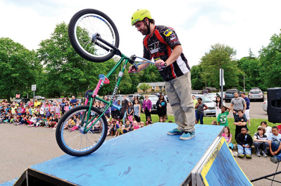 Hour photo / Erik Trautmann Dan Todd describes a proper safety check for bicycles as Fox Run Elementary School hosts the BMX troupe, Perfection On Wheels, Friday at the school.