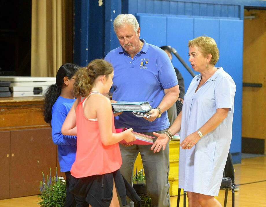 Hour Photo/Alex von Kleydorff Tracey School Principal Paul Krasnavage and Assistant Principal Alene LaMendola are presented with hand made memento books 'We are Tracey Cubs' from the students to mark their retirement during a program at the school on Monday morning