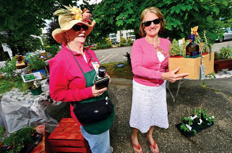 Hour photo / Erik Trautmann Member Marian Ainsworth sells Ann Marie Ekstrom an arraingement Norwalk Garden Club Plant Sale at 1 Park Saturday.
