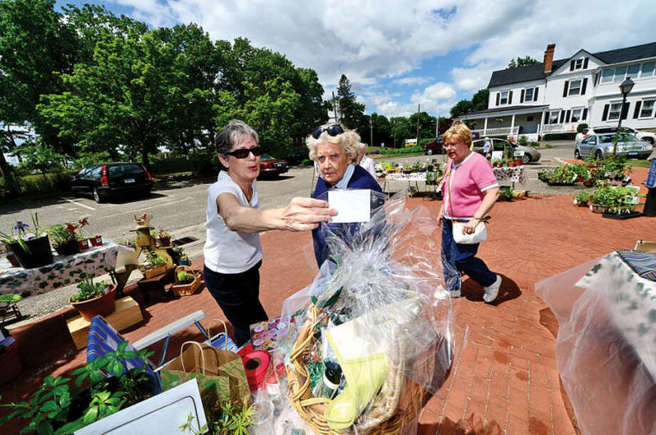 Hour photo / Erik Trautmann Members Diane Russell and Ginger Lancheck the raffle gift during the Norwalk Garden Club Plant Sale at the parking lot at 1 Park Saturday.