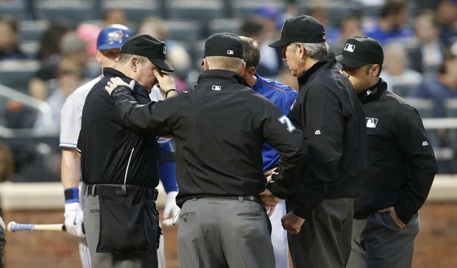 Umpires gather around home plate umpire Marty Foster, left, after he was hit in the jaw by a ball in the third inning of a baseball game a between the New York Mets and the Toronto Blue Jays in New York, Monday, June 15, 2015. (AP Photo/Kathy Willens)