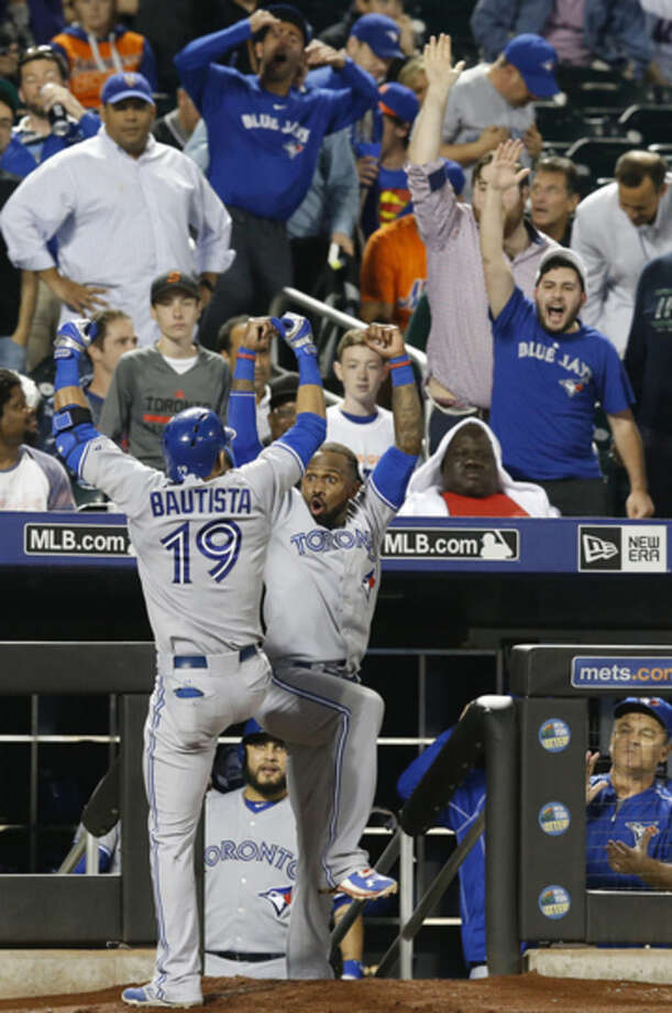 Toronto Blue Jays designated hitter Jose Bautista (19) celebrates with Jose Reyes after hitting an ninth inning, game-tying, solo home run in a baseball game against the New York Mets in New York, Monday, June 15, 2015. (AP Photo/Kathy Willens)