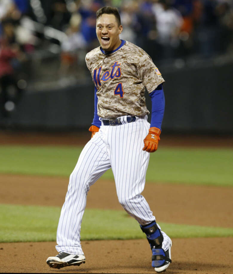 New York Mets Wilmer Flores (4) reactD after hitting an 11th-inning, walk-off, RBI single lifting the Mets to a 4-3 victory over the Toronto Blue Jays in a baseball game in New York, Monday, June 15, 2015. The Mets victory ended the Jays winning streak at 10. (AP Photo/Kathy Willens)