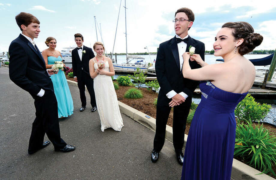 Hour photo / Erik Trautmann Norwalk High School students Rachel Baker pins a boutonniere on Thomas Henderson as James Henderson, Sarah Henderson, Nick Wargo and Emily Cox look on at Cove Marina Saturday before leaving for the prom.