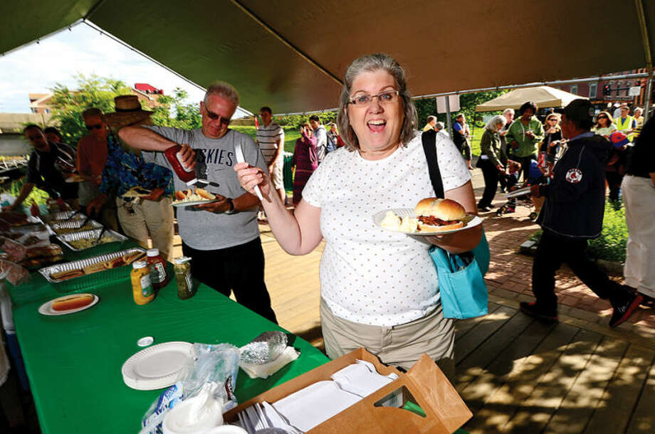 Patti Terpstra enjoys a free burger at the Norwalk Seaport Association's Commissioning Day reception at the Sheffield Island Ferry dock Saturday,