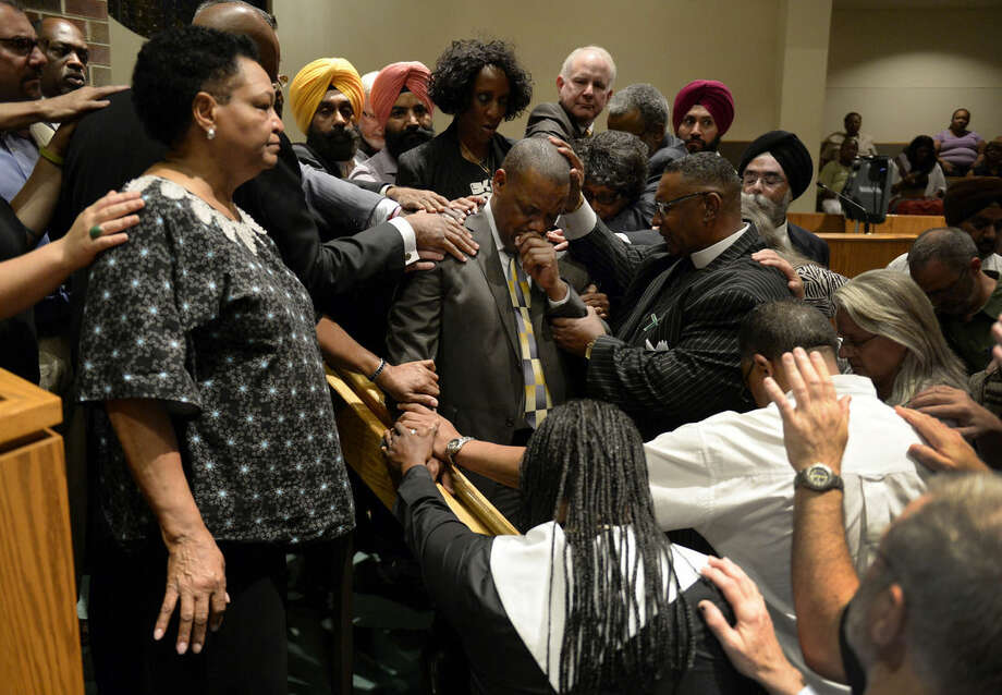 Religious leaders surround Rev. Dr. Timothy Tyler, at center with hand to face, Pastor at the Shorter Community African Methodist Episcopal Church, during a prayer vigil for victims of the shootings at a church in Charleston, S.C., Thursday, June 18, 2015, in Denver. (Andy Cross/The Denver Post via AP) MAGS OUT; TV OUT; INTERNET OUT; NO SALES; NEW YORK POST OUT; NEW YORK DAILY NEWS OUT; MANDATORY CREDIT
