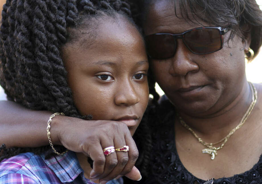Antonee Martin, left, and her mother Latrechia Jackson, right, visit the memorial site set up in front of the Emanuel AME Church, Thursday, June 18, 2015 in Charleston, S.C. Martin said her aunt Susie Jackson was one of the victims in the shooting Wednesday night at the church. (AP Photo/Stephen B. Morton)
