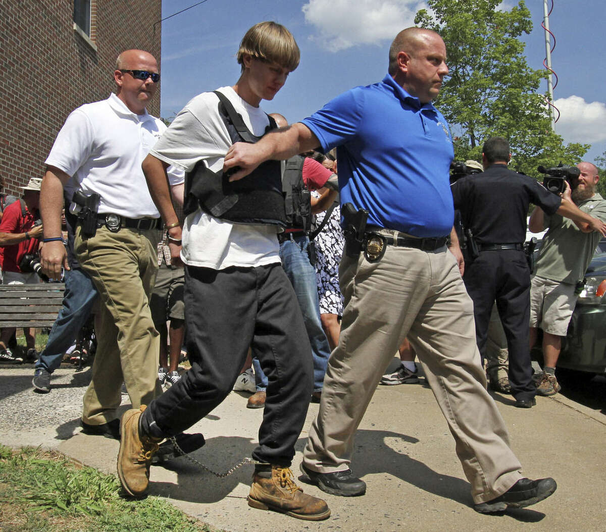 CORRECTS BYLINE TO BEN EARP FROM CHUCK BURTON - Charleston, S.C., shooting suspect Dylann Storm Roof, second from left, is escorted from the Shelby Police Department in Shelby, N.C., Thursday, June 18, 2015. Roof is a suspect in the shooting of several people Wednesday night at the historic The Emanuel African Methodist Episcopal Church in Charleston, S.C. (AP Photo/Ben Earp)