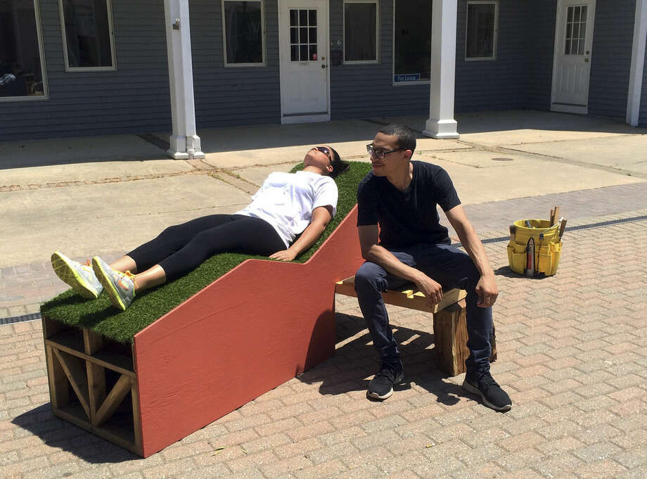 "In this Sunday, June 14, 2015 photo provided by New York City artist Jim Osman, his assistant Alex Reyes, right, sits beside a passer-by lying on the wood and tile ""Corbu Bench"" sculpture that Osman installed in Madison, Conn., as part of the town's 15th annual Sculpture Mile event. The sculpture was torn apart and put in a dumpster soon after the installation on Sunday by a maintenance worker, believing it was not allowed in the plaza. (Jim Osman via AP)"