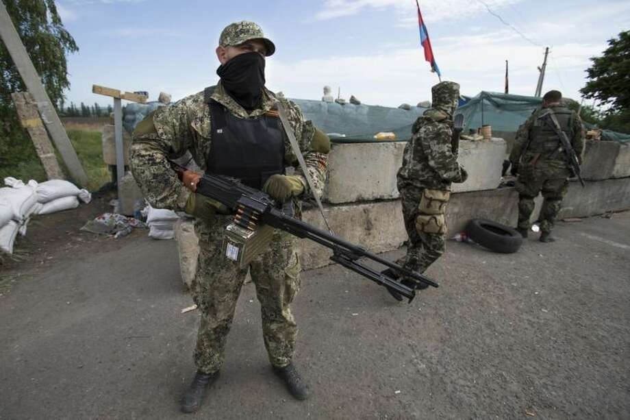 Pro-Russian armed militants guard a checkpoint blocking the major highway which links Kharkiv, outside Slovyansk, Ukraine, Saturday, May 24, 2014. Ukrainians vote Sunday in an early presidential election that could be a crucial step toward resolving the country's crisis, but separatists in the east are threatening to block the vote. The election, which comes six months after the outbreak of protests that led to the president's ouster and a deepening chasm between pro-Europe and pro-Russia Ukrainians, aims to unify the fiercely divided country or at least discourage further polarization.(AP Photo/Alexander Zemlianichenko)