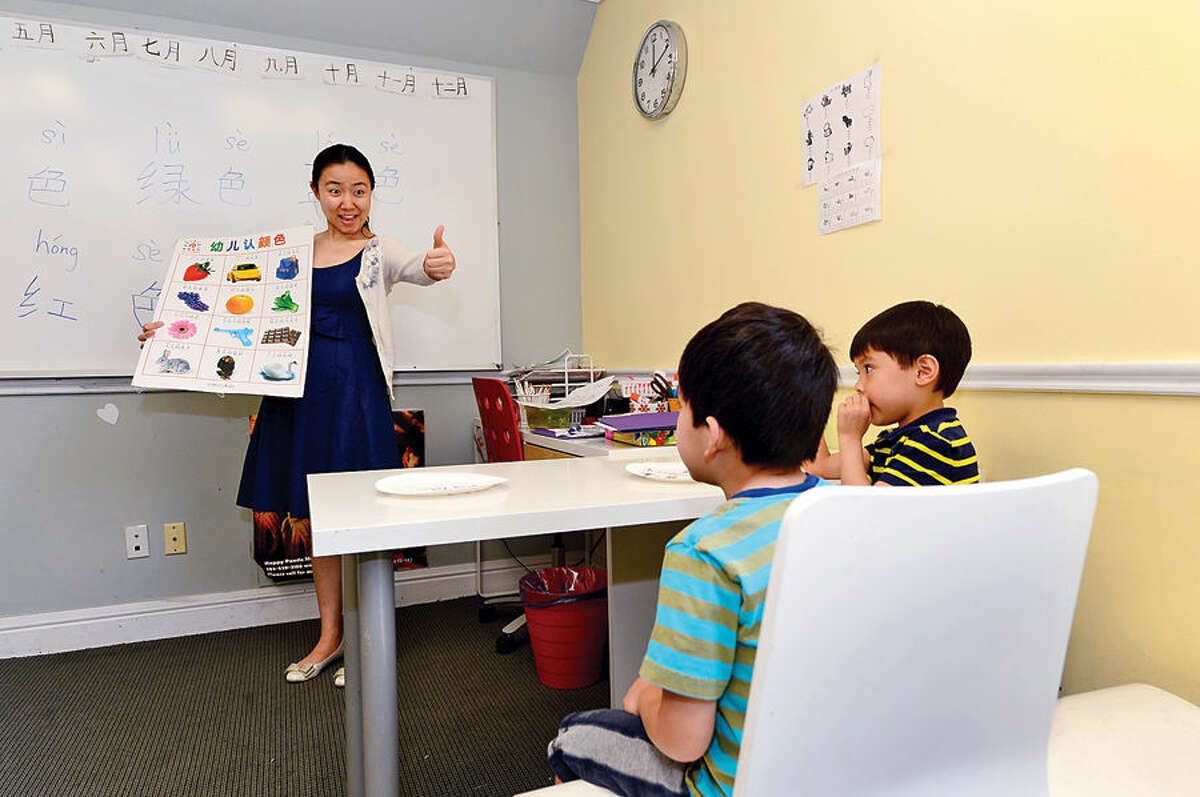 Niki Li, a teacher at Happy Panda Mandarin School in Wilton, works with students Alexander Mariani, 5, and Charles Lugo, 4, at the school Wednesday afternoon.