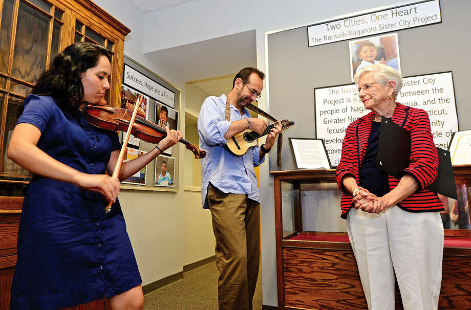 Hour photo / Erik Trautmann Norwalk/Nagarote Sister City Project director Tish Gibbs listens to Intakes Music's Angelica Durrell and Carlos Boltes play traditional music in the Mayor's Gallery as Norwalk's link with Sister Cities International and Nagarote, Nicaragua, are celebrated at City Hall on Friday morning.