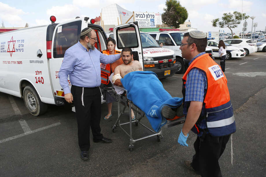 "Israeli medics wheel a man wounded in a shooting in the West Bank as he is brought to a hospital in Tel Aviv, Israel, Friday, June 19, 2015. The man was wounded when a gunman opened fire at a car outside a West Bank settlement, killing an Israeli man, in what police said was a ""terror attack."" (AP Photo/Tomer Appelbaum) ***ISRAEL OUT***"