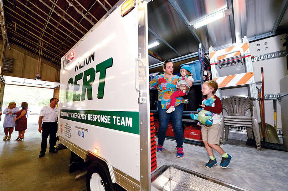 Wilton resident Tara Butzbaugh and her children Ben, 6, and CeCe, 2, check out the new CERT emergency response vehicle following the dedication of the box truck at a special ceremony at the Wilton Fire Department headquarters Wednesday.
