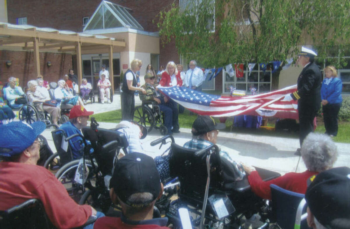 Contributed photo The American flag is folded during a ceremony honoring veterans Friday afternoon at Aurora Senior Living in Norwalk.