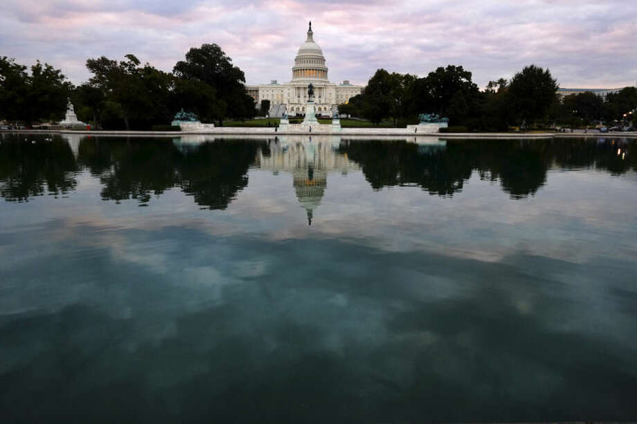 FILE - In this Oct. 1, 2013, file photo, the U.S. Capitol is mirrored in the Capitol Reflecting Pool on Capitol Hill in Washington. It's not news that Congress is gridlocked. What's increasingly striking is that both parties are nearly unanimous in their stands, with each one seemingly certain that its position is totally right and the other's is totally wrong. (AP Photo/J. David Ake, File)