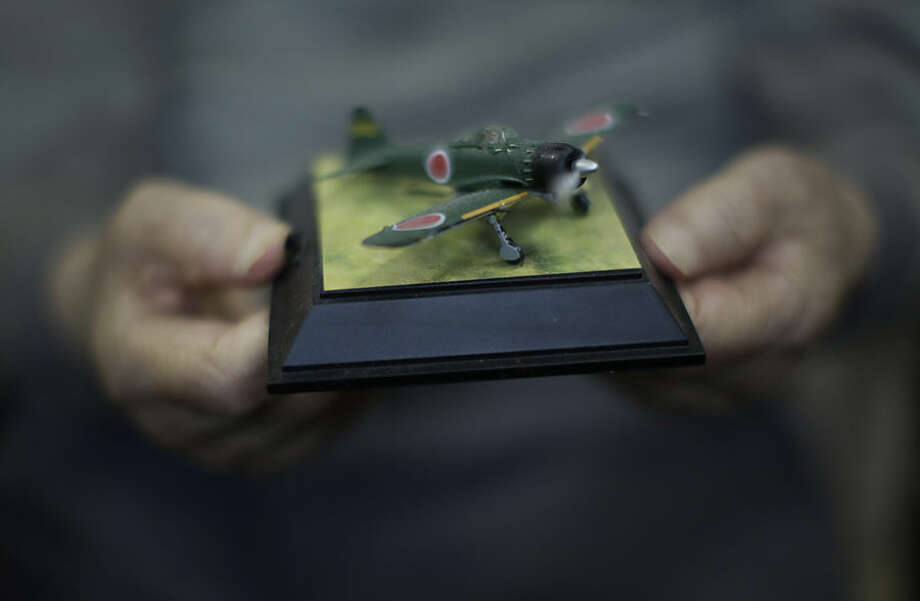 """In this April 23, 2015 photo, Hisashi Tezuka, a kamikaze who survived because the war ended, holds a miniature toy Zero, a gift from his daughter, and turns its buzzing propeller motor during an exclusive interview with the Associated Press at his home in Yokohama, south of Tokyo. He was the kamikaze, """"the divine wind,"""" ordered to fly their planes into certain death. The U.S. Strategic Bombing Survey and data kept at the library at Yasukuni shrine in Tokyo estimate that about 2,500 of them died during the war. Some history books give higher numbers. About one in every five kamikaze planes managed to hit an enemy target. (AP Photo/Eugene Hoshiko)"""