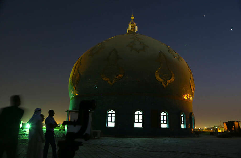 Iraqi Muslim men gather, on the roof of Imam Ali Mosque, waiting to see the crescent moon marking the beginning of Ramadan, at sunset in Basra, Iraq, Wednesday, June 17, 2015. Ramadan starts the day after the sighting of the crescent moon that marks the beginning of a new lunar month. (AP Photo/ Nabil al-Jurani)
