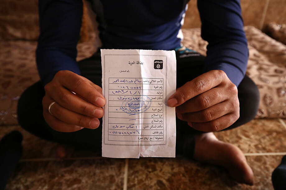 "In this Wednesday, May 27, 2015 photo, Salim Ahmed, a former Iraqi Army member, holds the ""repentance card"" he received from the Islamic State group in June 2014 shortly after the militants took over his home village of Eski Mosul in northern Iraq. The document is part of the apparatus of control the Islamic State group has constructed across its self-declared ""caliphate,"" the territory it conquered in Syria and Iraq. (AP Photo/Bram Janssen)"