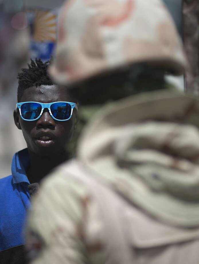 A young Haitian talks to a Dominican soldier as he waits to cross the border from Malpasse, Haiti into Jimani, Dominican Republic, Wednesday, June 17, 2015. Authorities are prepared to resume deporting non-citizens without legal residency in the Dominican Republic after largely putting the practice on hold for a year, the head of the country's immigration agency said Tuesday. For decades, the Dominican Republic has deported non-citizens, the vast majority of whom come from neighboring Haiti to work in low-wage jobs.(AP Photo/Rebecca Blackwell)