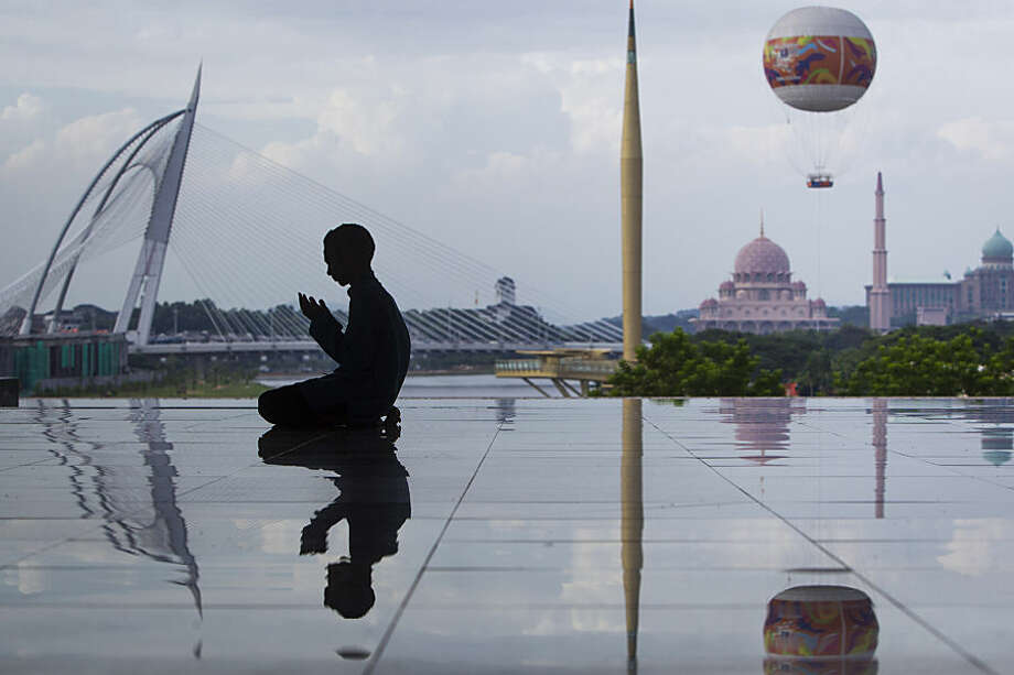 A Malaysian Muslim man is silhouetted as he performs his prayers at a mosque in Putrajaya, Malaysia Wednesday, June 17, 2015. During Ramadhan, Muslims refrain from eating, drinking, smoking and sex from dawn to dusk. Muslims are called to practice more actively the dictates of their faith such as tolerance, patience and an increase in works of charity. (AP Photo/Joshua Paul)