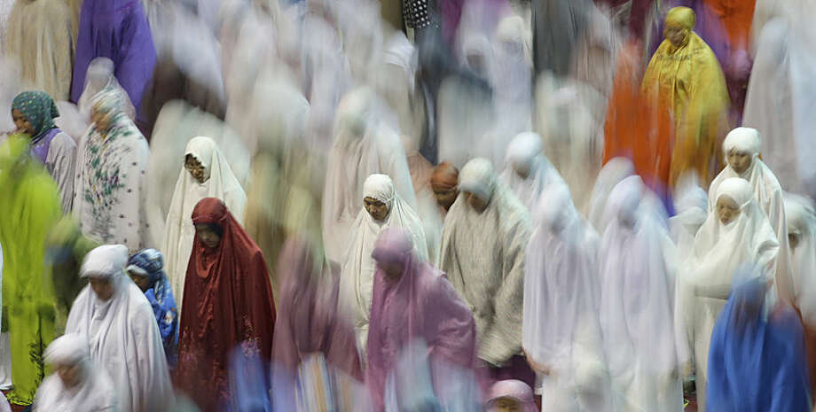 "In this photo taken using slow shutter speed, Muslim women offer an evening prayer called ""tarawih"" marking the first eve of the holy fasting month of Ramadan at Istiqlal Mosque in Jakarta, Indonesia, Wednesday, June 17, 2015. During Ramadan, the holiest month in Islamic calendar, Muslims refrain from eating, drinking, smoking and sex from dawn to dusk. (AP Photo/Dita Alangkara)"