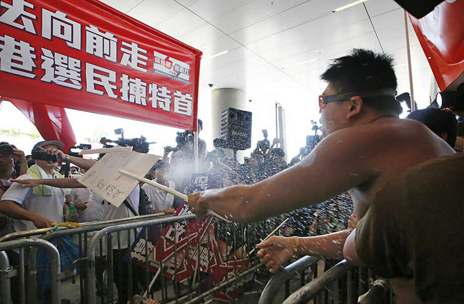 A pro-Beijing protester, center, sprays water to a pro-democracy protester, right, during a confrontation outside the Legislative Council in Hong Kong Wednesday, June 17, 2015. Hong Kong election reform proposals that sparked massive street protests last year in the southern Chinese financial center are set to be presented to lawmakers, who will likely reject them. (AP Photo/Kin Cheung)