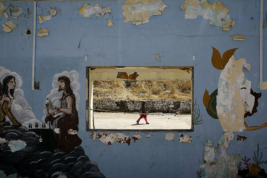 A girl walks at a refugee and migrant camp as graffiti is displayed on a wall of a former military base in the village of Moria on the northeastern Greek island of Lesvos on Wednesday, June 17, 2015. The Aegean island has borne the brunt of a huge influx of migrants from the Middle East, Asia and Africa crossing from Turkey to nearby Greek islands. More than 50,000 migrants have arrived in Greece so far this year. (AP Photo/Thanassis Stavrakis)