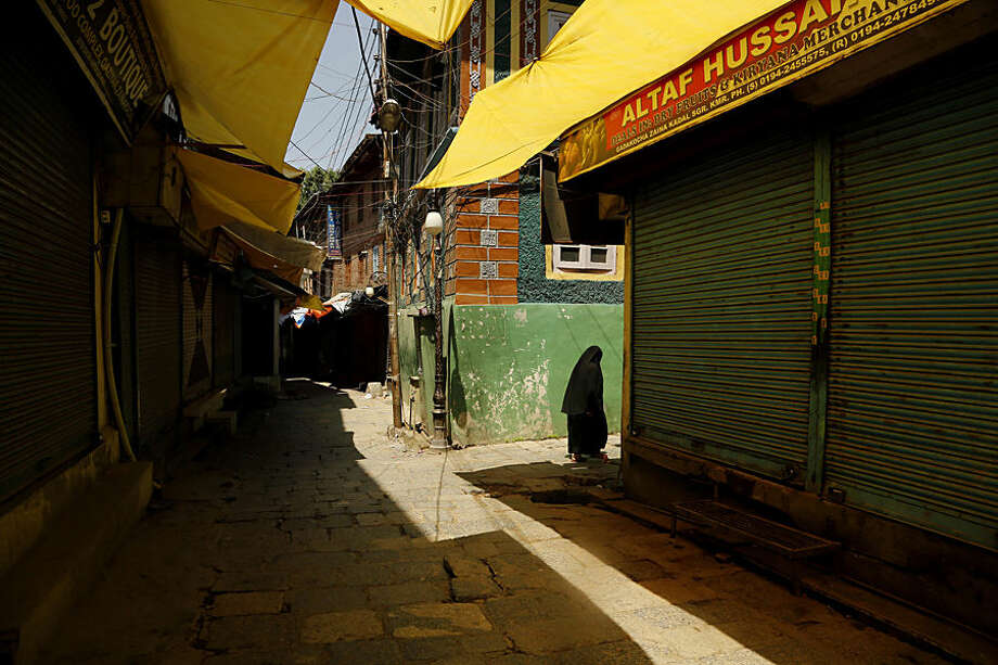 A Kashmiri woman walks through a closed market during a strike in Srinagar, Indian controlled Kashmir, Wednesday, June 17, 2015. Kashmiri separatists called for a complete shutdown across Kashmir on Wednesday, to protest the recent killings of civilians by unknown gunmen in the town of Sopore. (AP Photo/Mukhtar Khan)