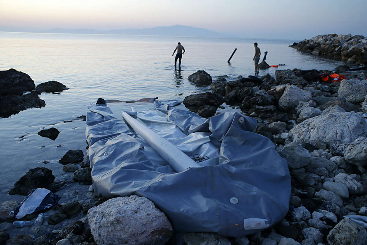 Syrian migrants look for their missing passports in the sea after their arrival on a small boat, foreground, from a Turkish coast to the Greek island of Lesvos in Mytilene, on Wednesday, June 17, 2015. Around 100,000 migrants have entered Europe so far this year as Italy and Greece have borne the brunt of the surge with many more migrants expected to arrive from June through to September. (AP Photo/Thanassis Stavrakis)