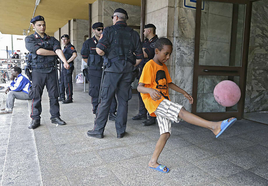 A young migrant plays with a ball in front of Italian policemen at the train station in Ventimiglia, Italy, Wednesday, June 17, 2015. European Union nations failed to bridge differences Tuesday over an emergency plan to share the burden of the thousands of refugees crossing the Mediterranean Sea, while on the French-Italian border, police in riot gear forcibly removed dozens of migrants.(AP Photo/Lionel Cironneau)