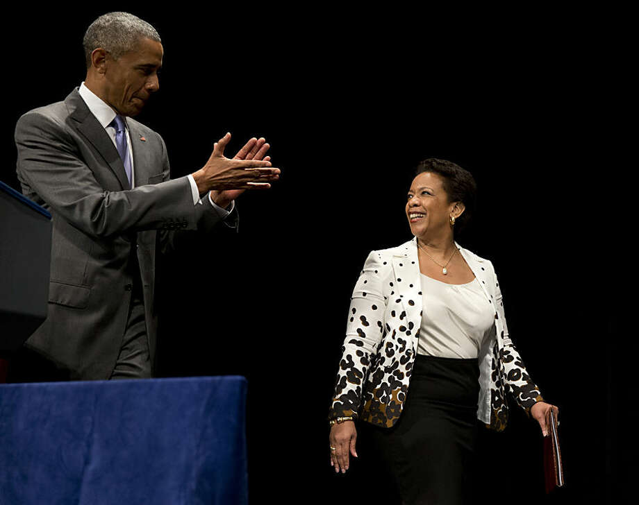 President Barack Obama applauds as Attorney General Loretta Lynch arrives for her investiture ceremony, Wednesday, June 17, 2015, at the Warner Theatre in Washington. Obama said Lynch is proving herself to be a tough but fair attorney general, and he says she sticks to following the law as her road map. (AP Photo/Carolyn Kaster)