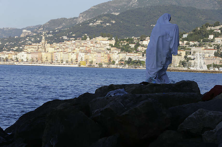 A migrant walks at the Franco-Italian border in Ventimiglia, Italy, Wednesday, June 17, 2015. Some 100 migrants, principally from Eritrea and Sudan, have attempted since last Friday, to cross the border from Italy into France but have been blocked by French and Italian police. (AP Photo/Lionel Cironneau)