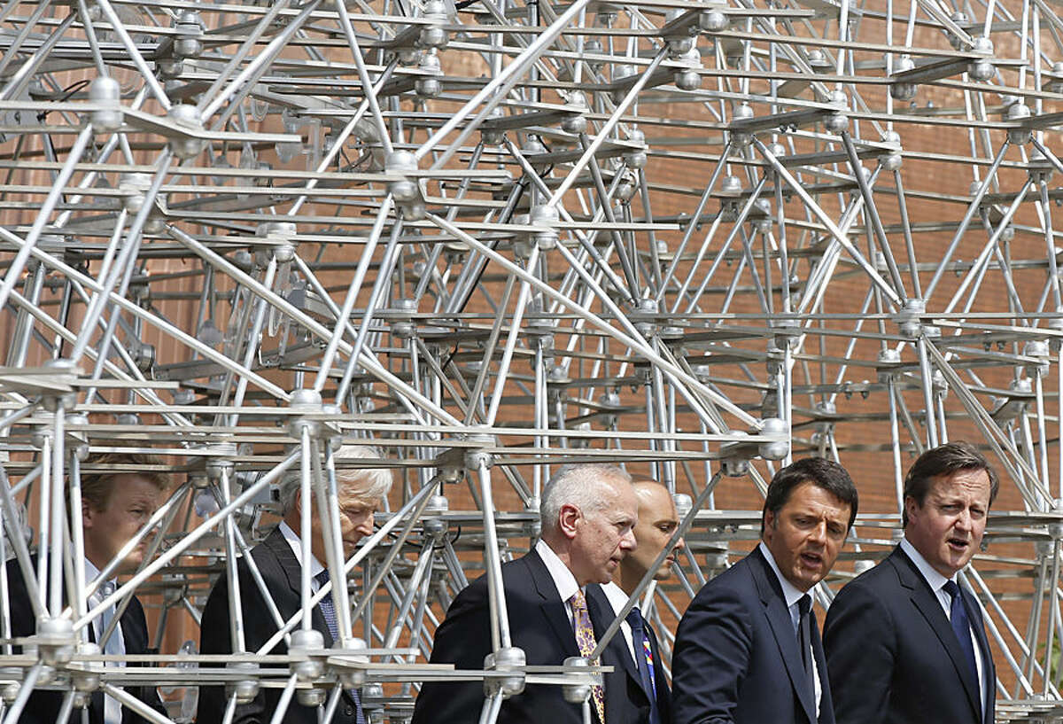 British Prime Minister David Cameron, right, flanked at left by Italian Premier Matteo Renzi, visit the British pavilion at the 2015 Expo in Rho, near Milan, Italy, Wednesday, June 17, 2015.(AP Photo/Luca Bruno)
