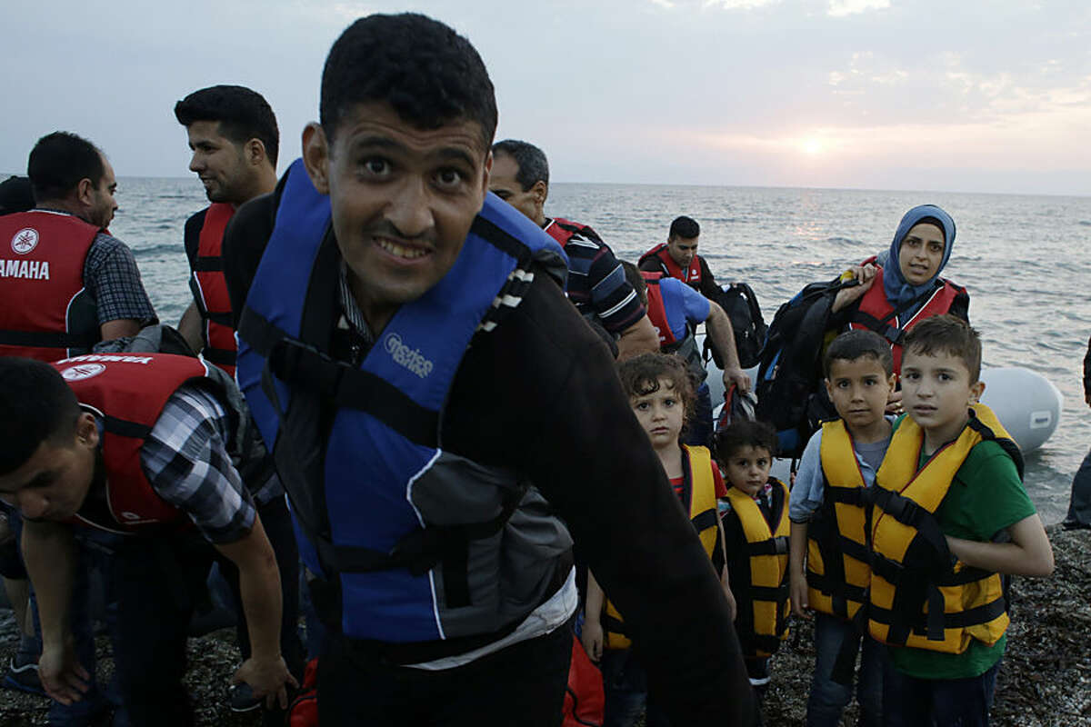 Syrian migrants react as they arrive in an overcrowded dinghy from the Turkish coast at a Mytilene beach, on the northeastern Greek island of Lesvos, early Thursday, June 18, 2015. Around 100,000 migrants have entered Europe so far this year, with some 2,000 dead or missing during their perilous quest to reach the continent. Italy and Greece have borne the brunt of the surge, with many more migrants expected to arrive from June through to September. (AP Photo/Thanassis Stavrakis)