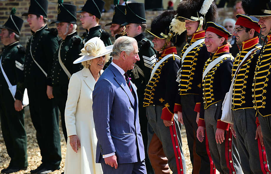 Charles, Prince of Wales, front right, and Camilla, Duchess of Cornwall view re-enactors as they attend the ceremonial opening of Hougoumont Farm in Braine-l'Alleud, near Waterloo, Belgium on Wednesday, June 17, 2015. The fully restored farm opens to the general public on June 18, 2015, which is the 200th anniversary of the Battle of Waterloo. (AP Photo/Emmanuel Dunand/Pool Photo via AP)