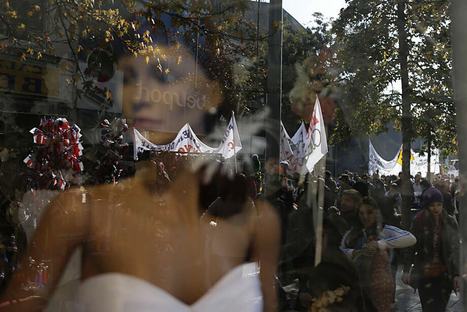 Protesting teachers and students are reflected in a store window in Santiago, Chile, Wednesday, June 17, 2015. A teachers union is in its second week on strike as they demand increased salaries and participation in educational reform. (AP Photo/Jorge Saenz)