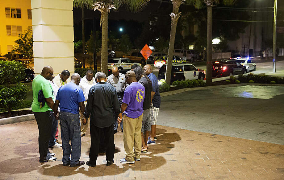 Worshippers gather to pray in a hotel parking lot across the street from the scene of a shooting Wednesday, June 17, 2015, in Charleston, S.C. (AP Photo/David Goldman)