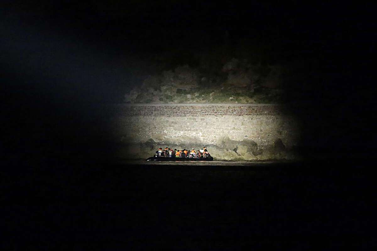 A Greek coast guard vessel uses a light to spot migrants arrive on an overcrowded dinghy from Turkish coasts during a patrol operation near the port of Mytilene on the Greek island of Lesvos, early Thursday, June 18, 2015. Around 100,000 migrants have entered Europe so far this year, with some 2,000 dead or missing during their perilous quest to reach the continent. Italy and Greece have borne the brunt of the surge, with many more migrants expected to arrive from June through to September. (AP Photo/Thanassis Stavrakis)